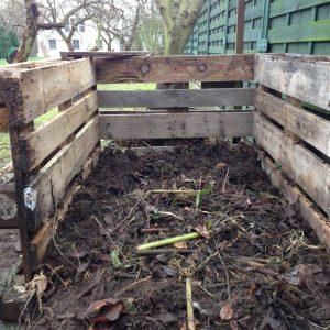 Aufschichten von Kompost in einem Eigenbau-Komposter